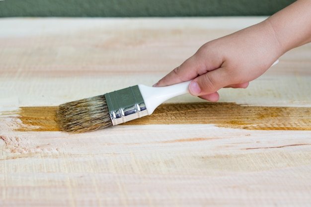 Mano de niño barnizar un estante de madera con pincel