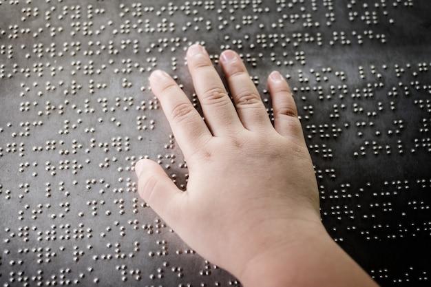 La mano del niño ciego tocando las letras braille en la placa de metal para entender