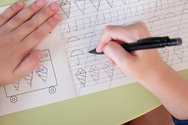La mano del niño escribe la receta en la mesa