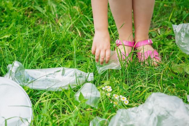 La mano del niño limpia la hierba verde de la basura plástica en el parque