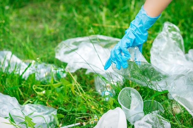 La mano del niño limpia el parque de desechos plásticos que yacen sobre la hierba verde
