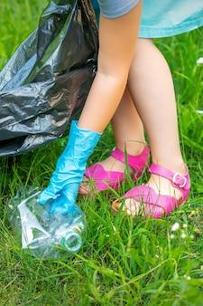 La mano del niño limpia el parque de utensilios de plástico en el césped del parque
