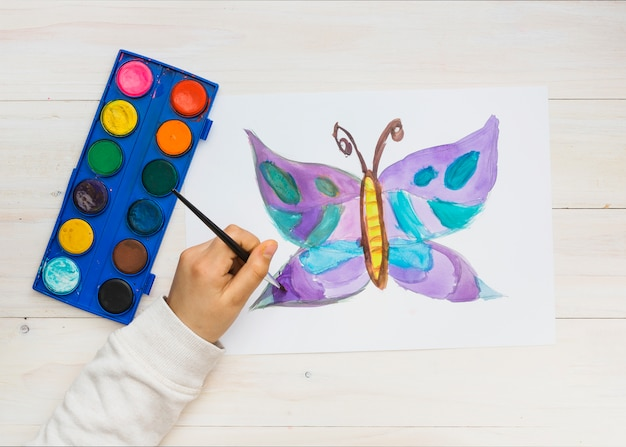 Mano de niño pintando hermosa mariposa dibujo en hoja blanca