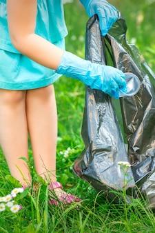 La mano del niño pone los desechos de plástico en la bolsa de basura en el parque