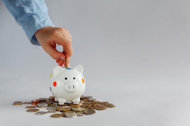 La mano del niño puso en las monedas blancas del dinero del piggybank.