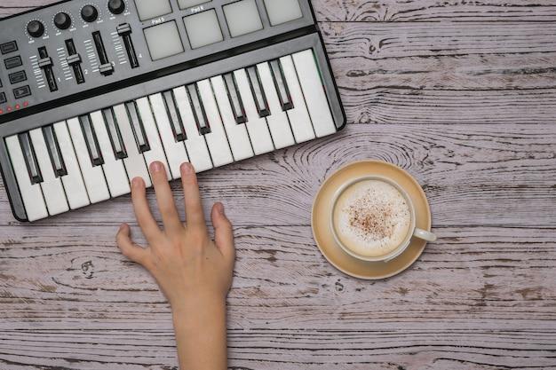 La mano de un niño sobre las teclas de una batidora de música y una taza de café en una mesa de madera. el proceso de crear música