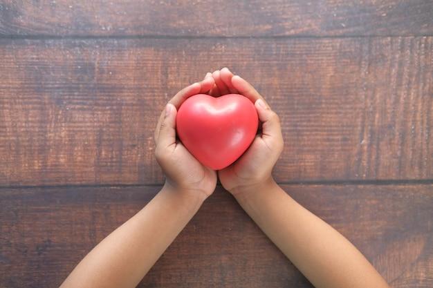 Mano de niño sosteniendo corazón rojo en la mesa de madera