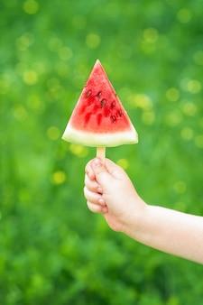 La mano de un niño está sosteniendo una rebanada triangular de una sandía sobre un fondo verde de la naturaleza