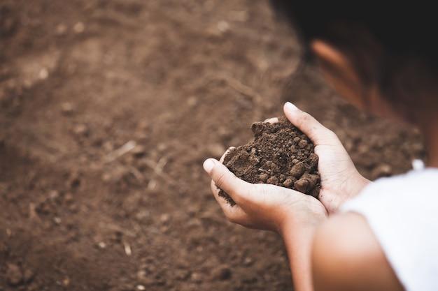 La mano del niño sosteniendo el suelo en forma de corazón se prepara para plantar el árbol