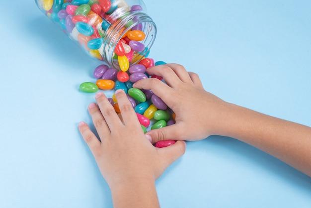 Mano del niño sosteniendo varios jelly beans sobre fondo azul.