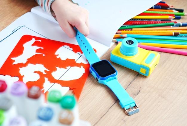 Mano de los niños sosteniendo un reloj inteligente con escuchas telefónicas, monitoreo remoto y rastreador gps.