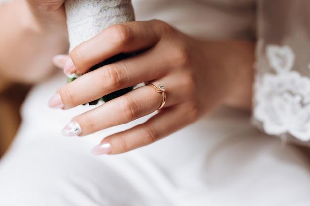 La mano de la novia con un anillo de compromiso minimalista con un diamante.