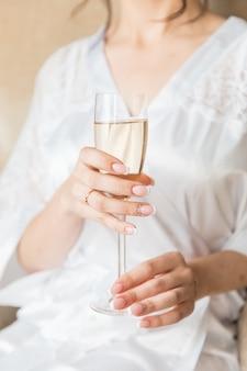 Mano de novia con hermosa manicura y anillo de compromiso y copa de champán