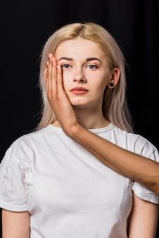 La mano del novio en la mejilla rubia de la mujer joven contra fondo negro
