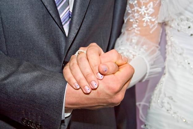 Mano del novio y la novia con anillos de boda