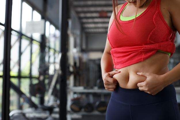 Mano obesa de la mujer que sostiene la grasa abdominal excesiva aislada en fondo del gimnasio.