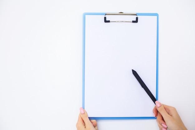 Mano de oficina sosteniendo una carpeta con un papel de color blanco sobre el fondo de la mesa blanca