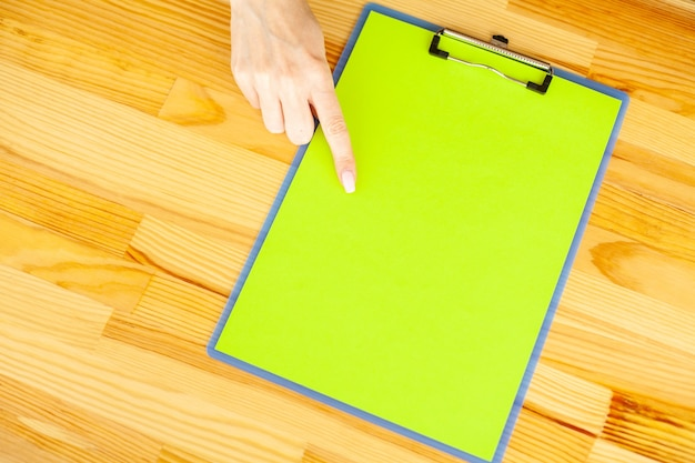 Mano de oficina sosteniendo una carpeta con un papel de color verde en el fondo de la mesa de madera.