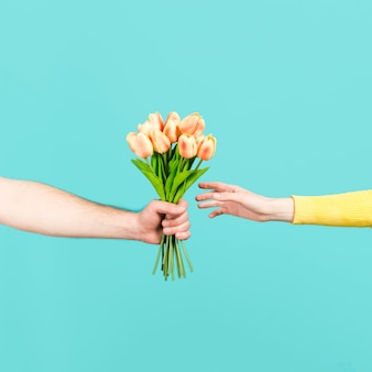 Mano ofreciendo ramo de flores