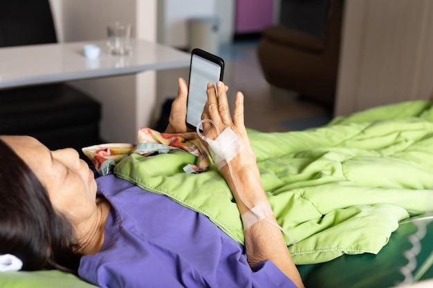 Mano del paciente mayor con inyección de solución salina acostado con teléfono celular en el hospital