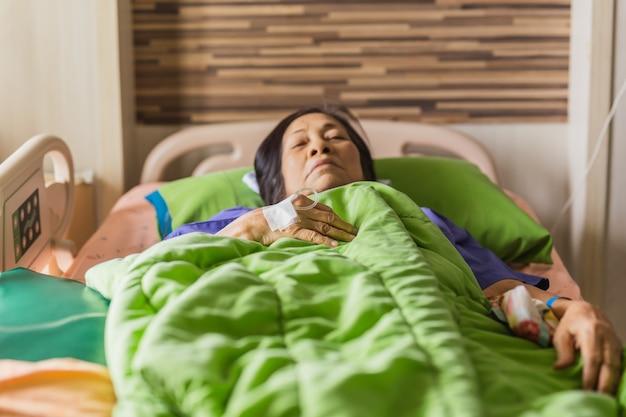 Mano del paciente mayor con inyección de solución salina en la cama del hospital