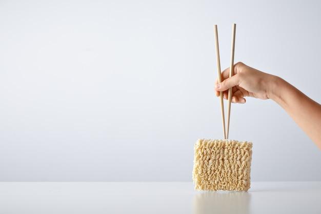 Mano con palillos encima del paquete de fideos de huevo secos prensados aislados en blanco