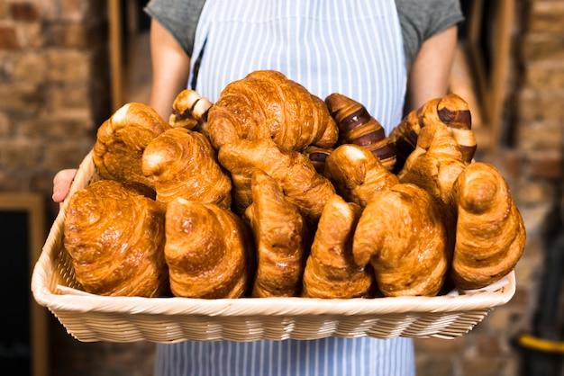 Mano del panadero femenino que sostiene la cesta de croissant al horno