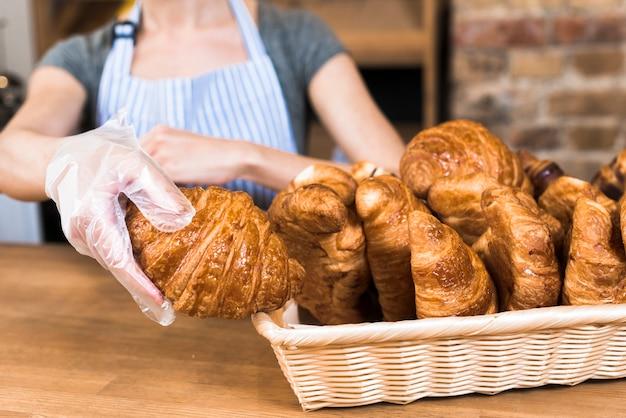 Mano de panadero femenino usando guantes de plástico que toman croissant horneado de la canasta