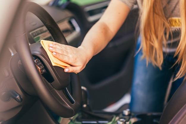 Mano con paño de microfibra para limpieza de carro.
