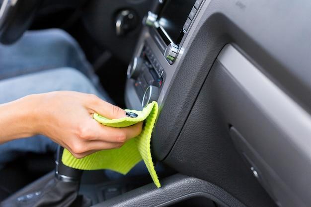 Mano con paño de microfibra de limpieza de coches