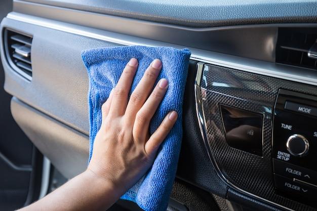 Mano con paño de microfibra de limpieza interior de automóvil moderno.