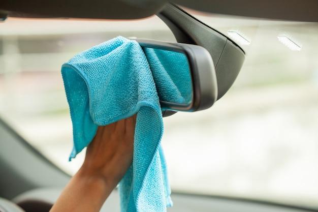 Mano con paño de microfibra limpieza interior coche moderno.
