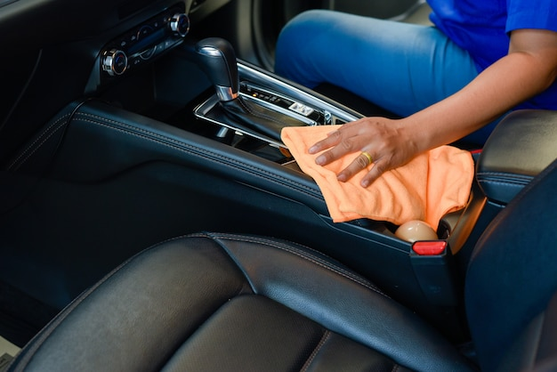 Mano con paño de microfibra limpieza interior del coche.