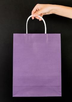 Mano con el paquete de compras púrpura