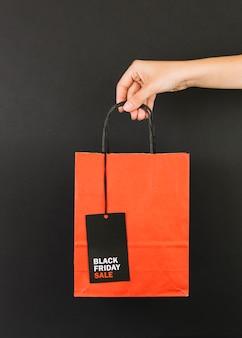 Mano con paquete rojo y etiqueta de venta