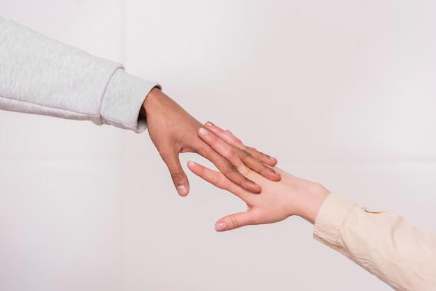Mano de la pareja interracial contra el fondo blanco