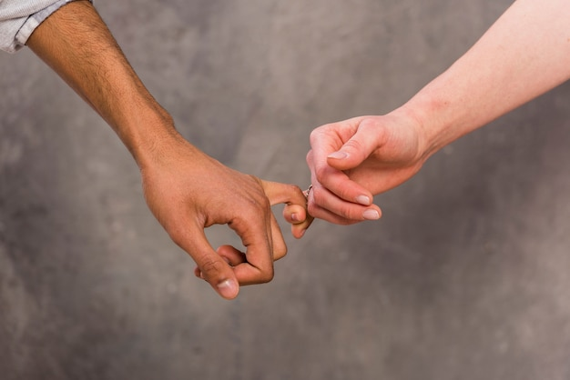 La mano de la pareja interracial sosteniendo el dedo de la otra contra un fondo de hormigón