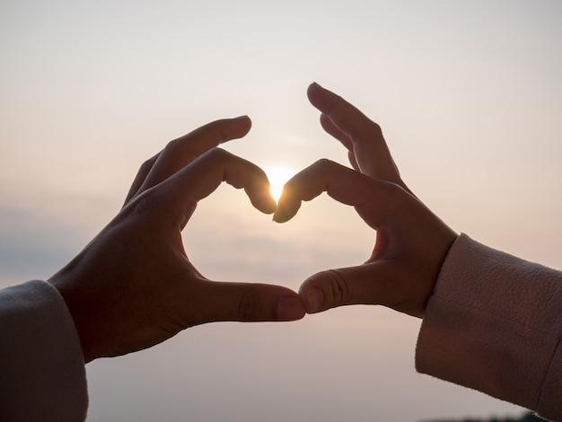 La mano de la pareja tiene forma de corazón. entre el fondo del cielo y el sol