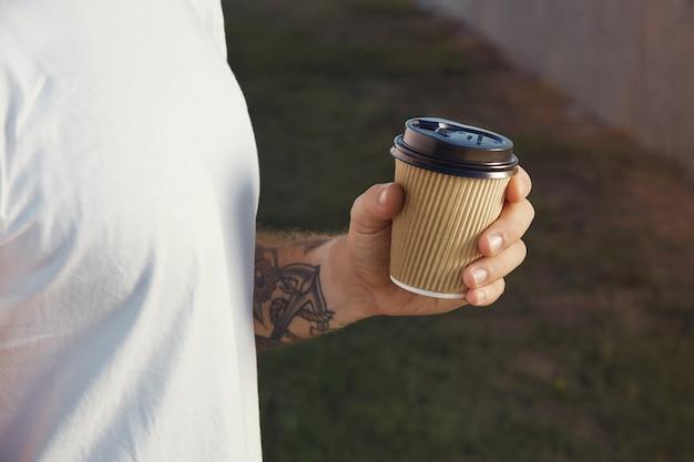 Mano y pecho de un hombre tatuado blanco vestido con camiseta blanca sin etiqueta sosteniendo una taza de café de papel marrón claro
