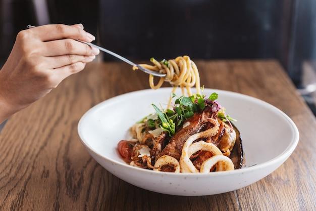 Mano pellizcando spaghetti seafood y levantado con un tenedor: spaghetti con langostinos, calamares, mejillones cocidos en aceite de oliva, chiles y ajo.