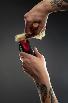 Mano de peluquero con equipo en mesa negra.