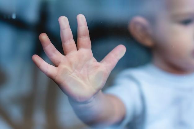 La mano pequeña del niño se presiona contra el cristal de la ventana con reflejo. soledad de los niños. orfanato y huérfanos.