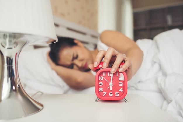 Mano perezosa de la mujer que sostiene el despertador en la cama