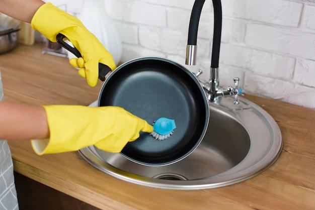 Una mano de persona con guante amarillo lavando sartén con cepillo en la cocina