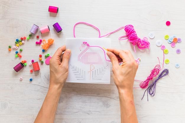 Una mano de persona haciendo bordados con elementos decorativos sobre fondo texturizado.