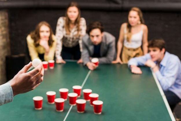 Mano de la persona con el objetivo de bola para juego de cerveza pong