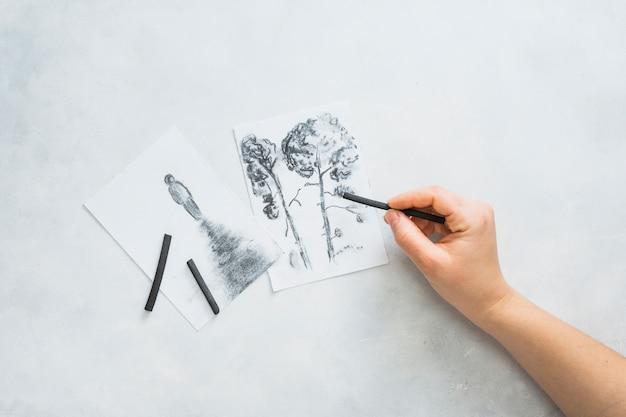 La mano de la persona que dibuja un hermoso dibujo con un palo de carbón en una superficie blanca