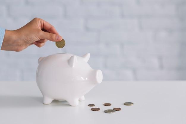 La mano de una persona que inserta la moneda en el piggybank blanco en el escritorio
