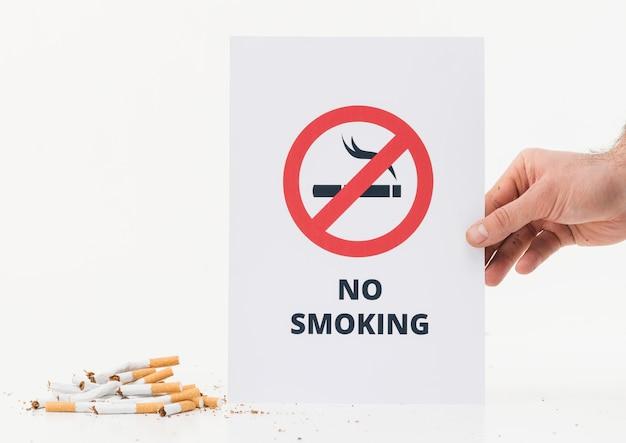 Mano de una persona que muestra el letrero de no fumar cerca de los cigarrillos rotos sobre fondo blanco