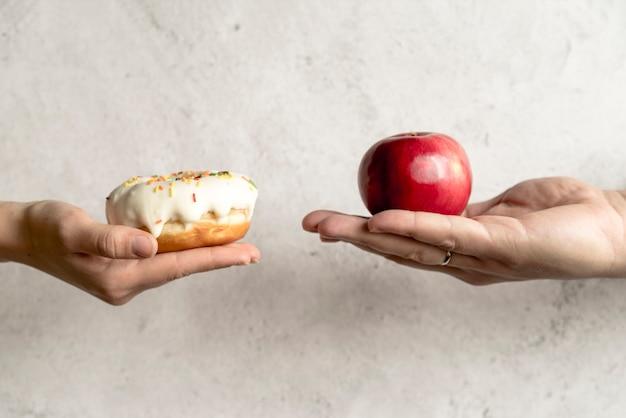La mano de la persona que muestra una rosquilla y una manzana frente a un fondo de concreto